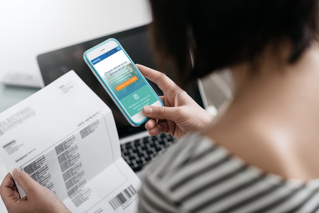 Woman checking an electricity bill, she is making a contactless payment using her smartphone; Shutterstock ID 423239392; Purchase Order: -